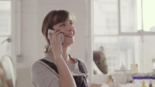 Female artist talks on mobile phone in art studio.