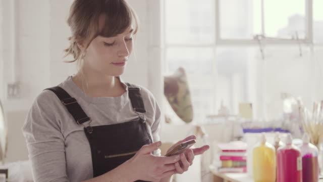 Female artist using internet on phone in art studio.