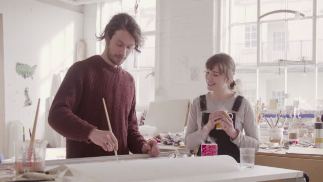 Female artist walks in art studio with cups of tea, where male artist is painting at table.