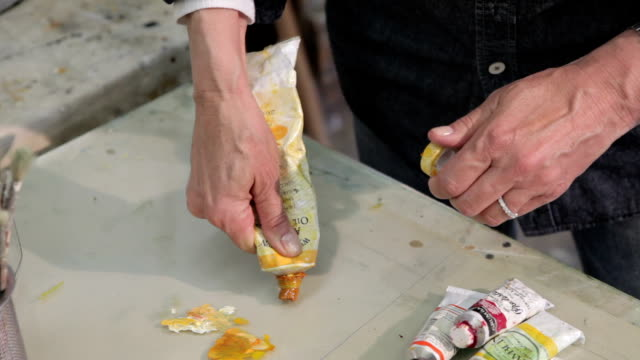 Female artist's hands squeezing yellow oil paint out onto glass