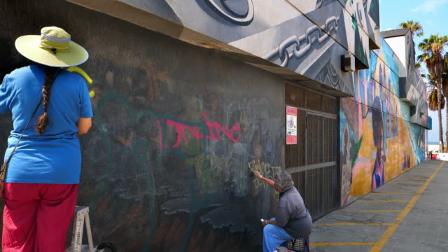 female artists removing graffiti on the wall in venice beach, los angeles, california, 4k - removing stock videos & royalty-free footage