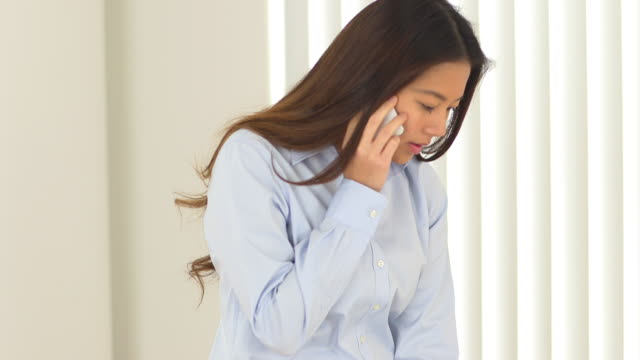 Female Asian businesswoman talking on the phone while working on laptop