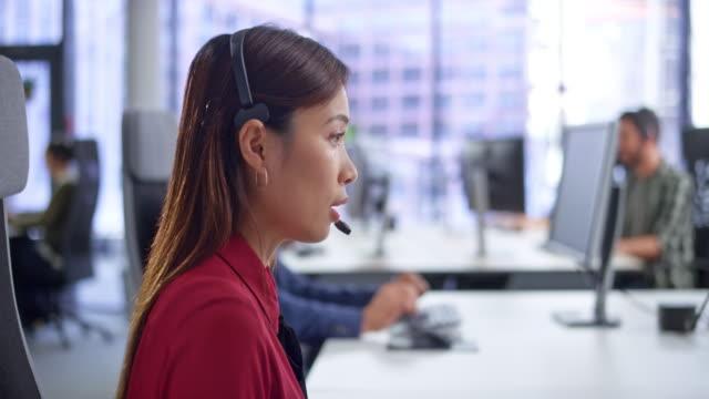 近代的なオフィスで彼女の机で顧客サービスを提供するld女性アジアのコールセンターエージェント - コールセンター点の映像素材/bロール