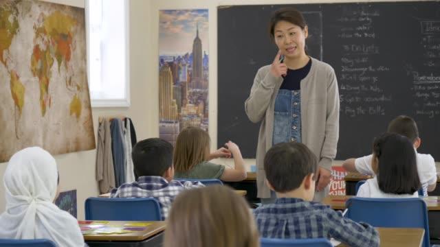 vidéos et rushes de femme asiatique élémentaire enseignant parlant aux étudiants - élève du primaire