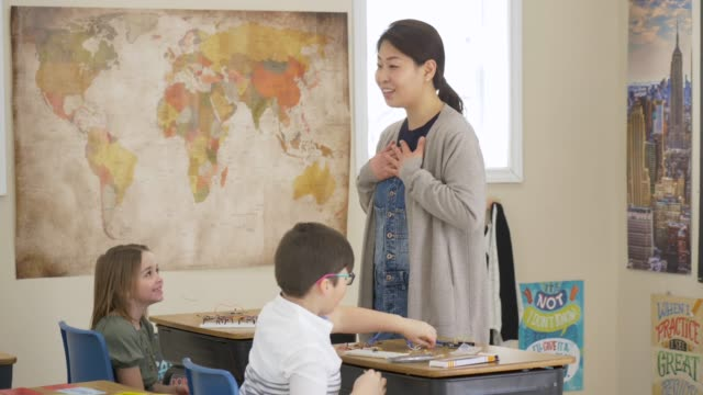 female asian elementary teacher speaking to students - fatcamera stock videos & royalty-free footage