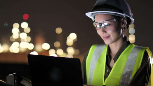 female asian engineer using laptop for engineer job in oil industrial plant at night, engineer working - occupational safety and health stock videos & royalty-free footage