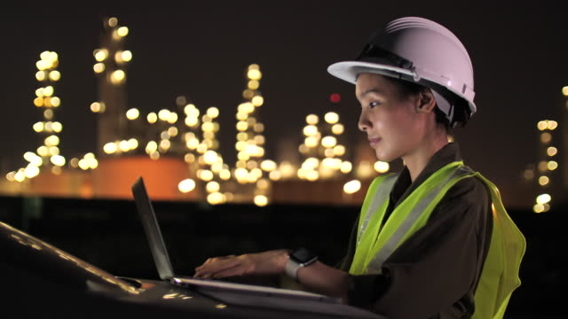 female asian engineer working with laptop at industrial at night - industrial building stock videos & royalty-free footage