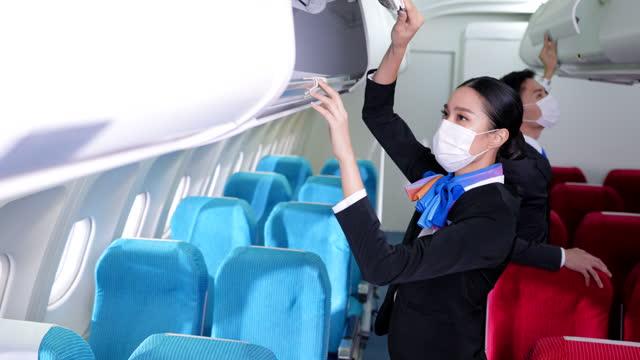 vídeos de stock, filmes e b-roll de comissária de bordo asiática, aeromoça com máscara protetora verificando a tampa do compartimento de bagagem depois que todos os passageiros estão embarcando e se preparando para uma nova viagem - 20 29 years