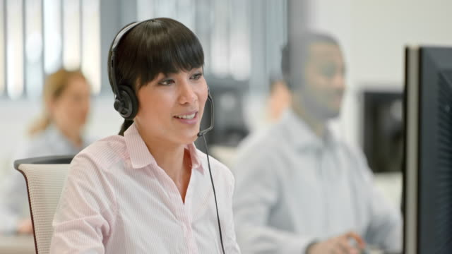 ds female asian helpline operator greeting the client over phone - headset stock videos & royalty-free footage
