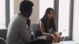 Female asian mentor teaching african intern helping with computer work