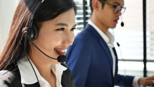 vidéos et rushes de femme asiatique téléphoniste répondant à l'appel - casque téléphonique