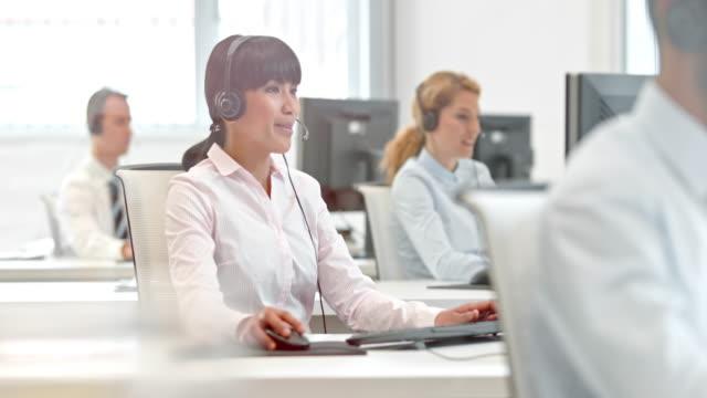 DS weibliche asiatische Telefon operator Arbeiten an Ihrem Schreibtisch