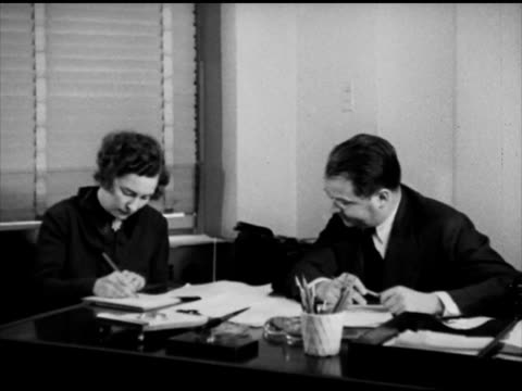 Female assistant sitting down w/ News Bureau manager unidentified manager dictating about 'tense negotiations' Rockefeller Center RCA Building...