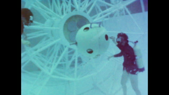 Female astronauts practice maneuvering objects underwater