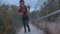 Female athlete climbing up the steps