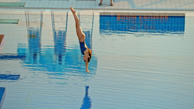 slo mo female athlete diving from a high platform at a competition - diving platform stock videos and b-roll footage