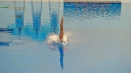 SLO MO Female athlete diving from a high platform in a competition