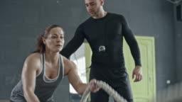 Female Athlete Doing Battle Rope Exercise with Coach