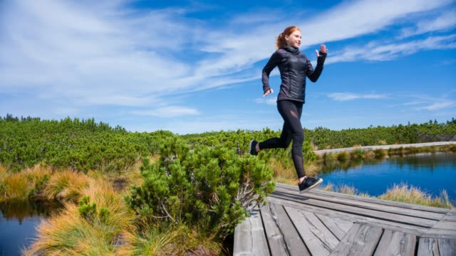 female athlete doing cardio exercises, jogging in nature - athlete stock videos & royalty-free footage