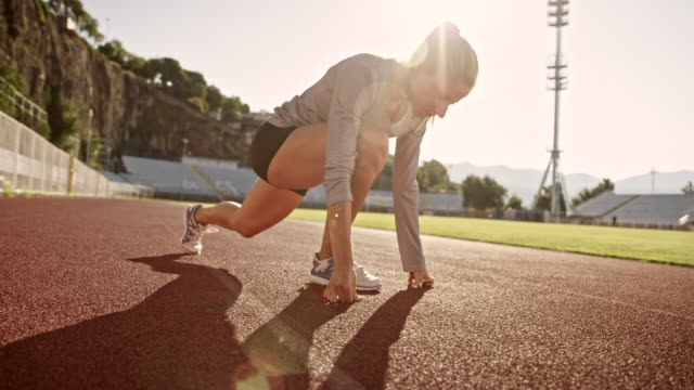 slo mo female athlete doing stretching exercises in the sunny stadium - athlete stock videos & royalty-free footage