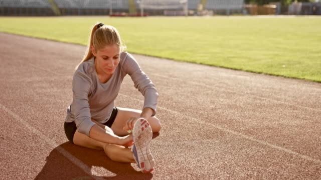 slo mo female athlete doing stretching exercises sitting on the track in the stadium - stretching stock videos & royalty-free footage