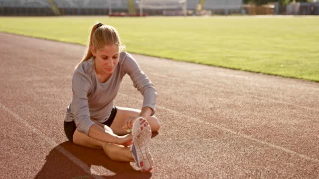 SLO MO Female athlete doing stretching exercises sitting on the track in the stadium