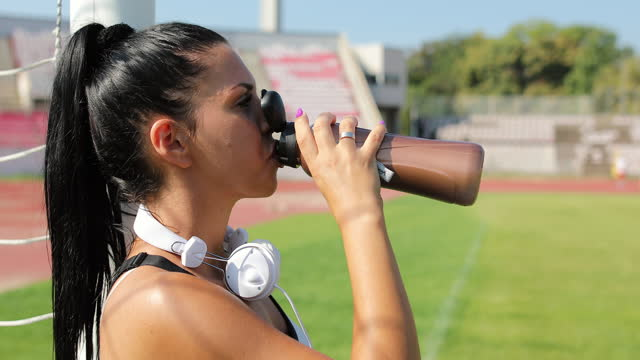 female athlete drinking water after successful training outdoors - bottle stock videos & royalty-free footage