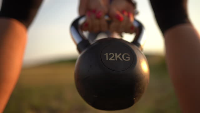 female athlete exercising with kettlebell in nature with her instructor - sports training stock videos & royalty-free footage