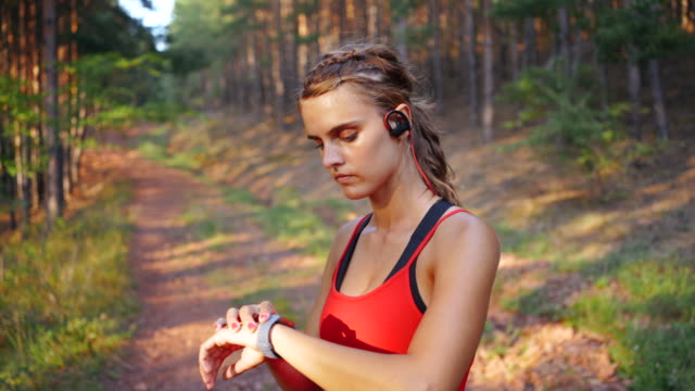 female athlete is looking at fitness tracker. - cross country running stock videos & royalty-free footage