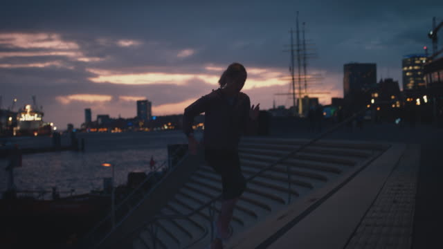 female athlete jogging up on staircase at harbor - steps and staircases stock videos & royalty-free footage