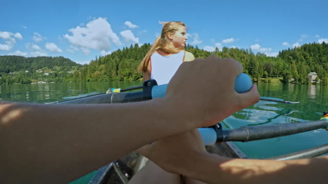 pov female athlete moving in a double scull while rowing behind her team mate - canottaggio senza timoniere video stock e b–roll