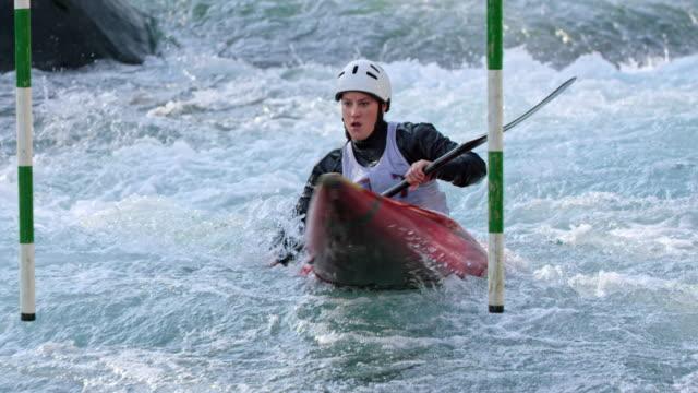 vidéos et rushes de slo mo athlète féminine naviguant son kayak dans une compétition de slalom - canoë