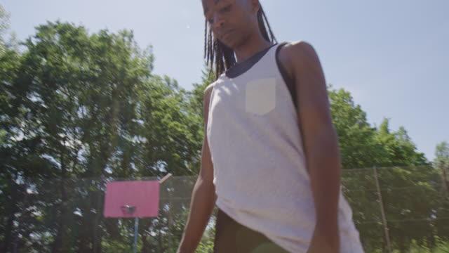vidéos et rushes de athlète féminin pratiquant le basket-ball le jour ensoleillé - streetball