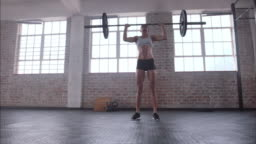 Female athlete practicing deadlift with weight bar
