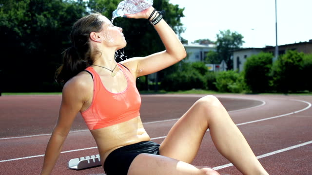 hd super slow-mo: female athlete refreshing with water - sweat stock videos & royalty-free footage