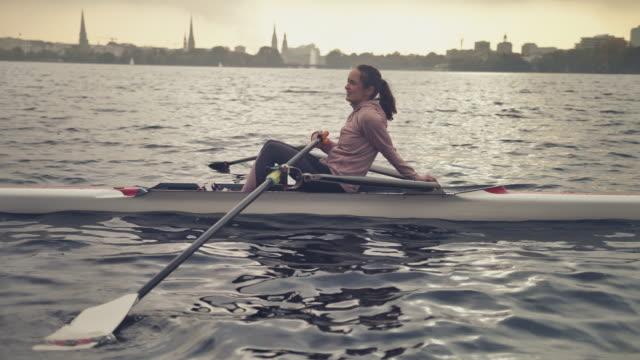 vídeos y material grabado en eventos de stock de atleta femenina descansando en bote de remos en el río - remo con espadilla