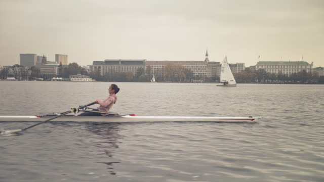 female athlete rowing boat in river against sky - sculling stock videos & royalty-free footage