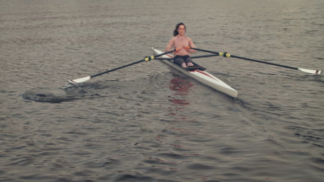 female athlete rowing boat in river - one young woman only stock videos & royalty-free footage