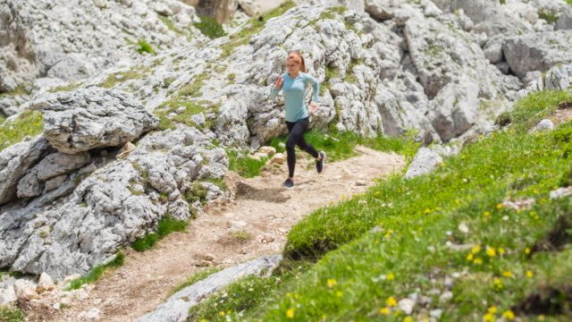 female athlete runner trail running in mountain terrain - off the beaten path stock videos & royalty-free footage