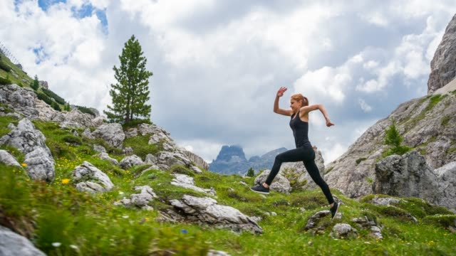 female athlete running on a grassy and rocky trail on a meadow, surrounded by mountains - young women stock videos & royalty-free footage