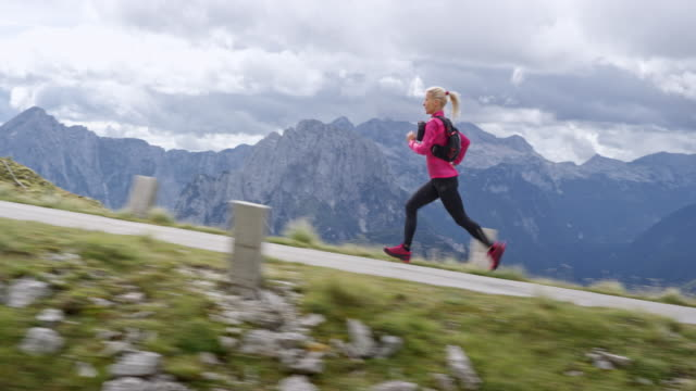 slo mo ts female athlete running on a high mountain road in sunshine - cardiovascular exercise stock videos & royalty-free footage