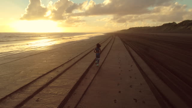 female athlete running on beach during sunset. - wellbeing stock videos & royalty-free footage