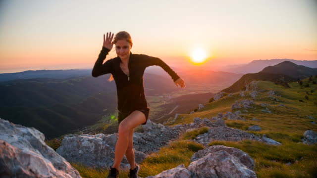 Female athlete running on rocky terrain in mountains at sunset