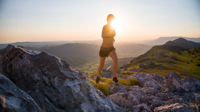 female athlete running on rocky terrain in mountains at sunset - in salita video stock e b–roll