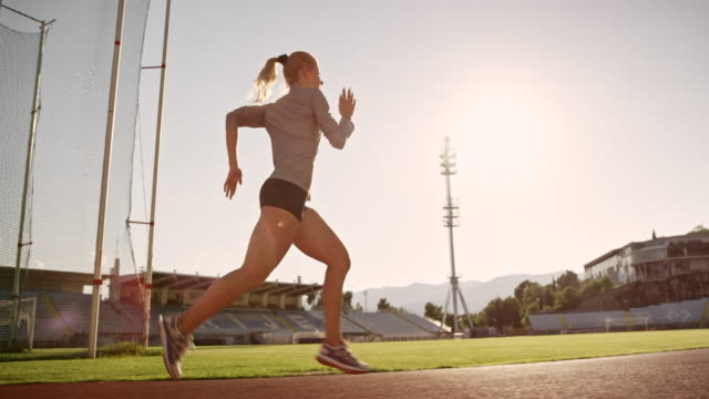 slo mo ts female athlete running on the track in sunny stadium - pista di atletica leggera video stock e b–roll