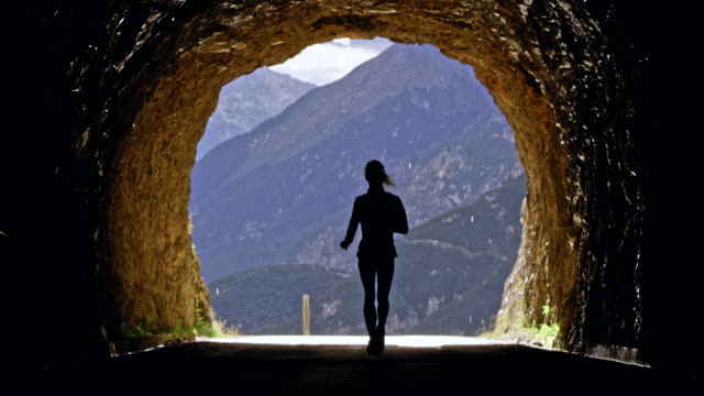 ld female athlete running through a tunnel high in the mountains on a sunny day - fade out video transition stock videos & royalty-free footage