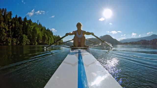 POV Female athlete sculling across a lake in a double scull
