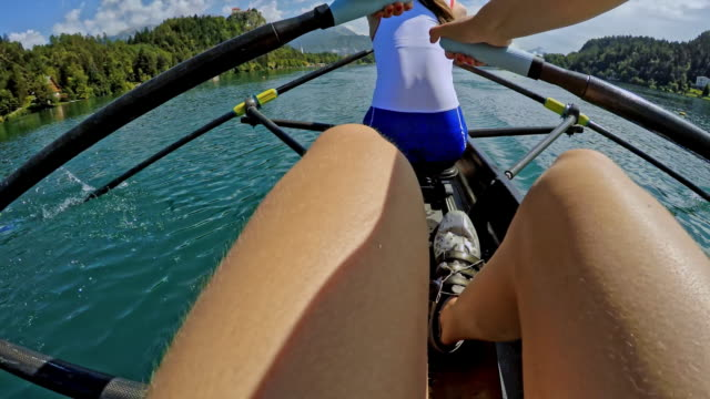 pov female athlete sculling on a lake behind her team mate in their double scull - scull stock videos & royalty-free footage