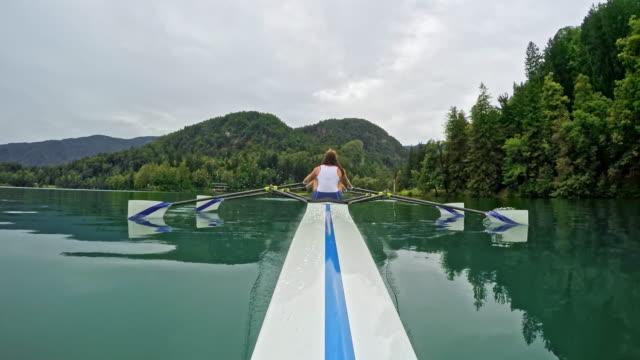 vídeos y material grabado en eventos de stock de atleta femenina de pov remar en un lago en doble scull - remo con espadilla