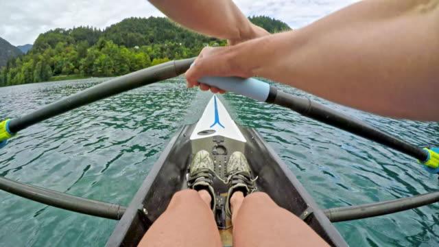 pov female athlete sculling on a lake - canottaggio senza timoniere video stock e b–roll